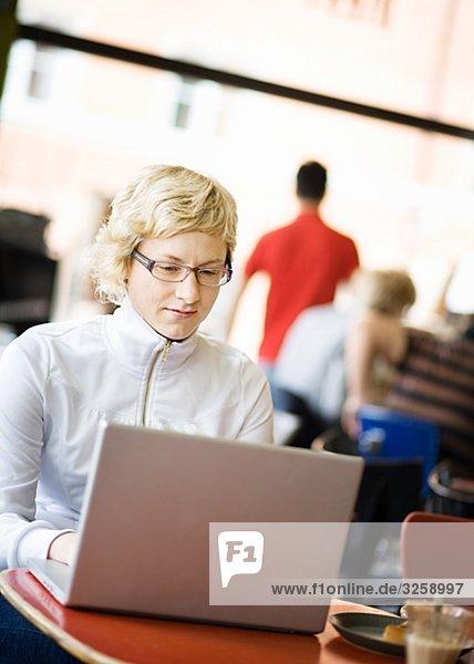 Frau mit einem Laptop in einem Café  Schweden.