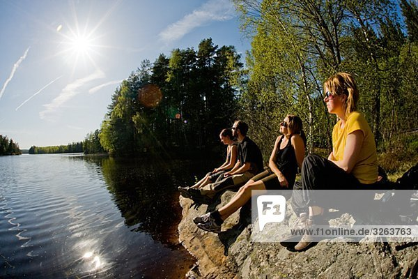 Four persons sitting by a lake  Sweden.