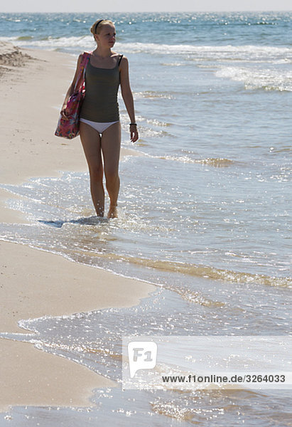 A teenage girl walking on the beach  Sweden.