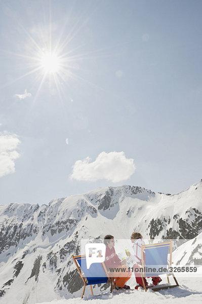 Österreich  Salzburger Land  Junges Paar im Liegestuhl sitzend  Gläser haltend