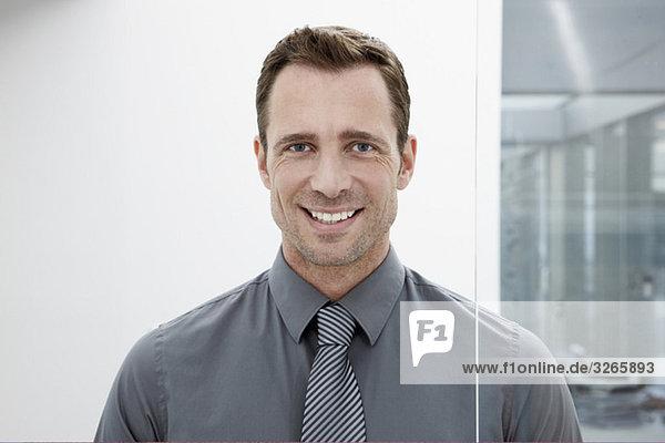 Deutschland  Köln  Geschäftsmann neben der Glastür  lächelnd  Portrait  Nahaufnahme