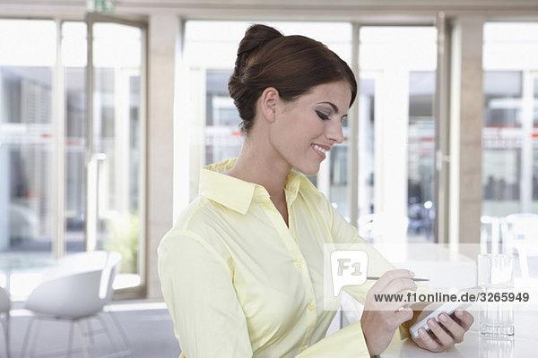 Geschäftsfrau im Büro mit Handheld  lächelnd  Portrait