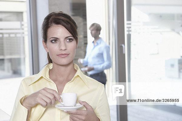 Geschäftsfrau im Büro bei einer Kaffeepause  Geschäftsmann im Hintergrund