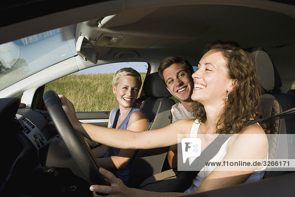 Deutschland  Bayern  Jugendliche beim Autofahren  Lachen  Seitenansicht  Porträt