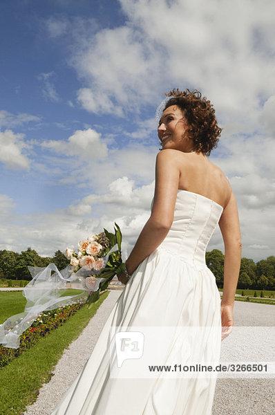 Deutschland  Bayern  Braut im Park mit Blumenstrauß  Portrait