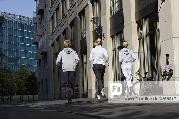 Germany  Berlin  Three friends jogging together