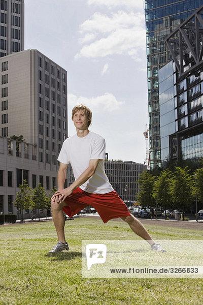 Junger Mann  der sich auf dem Rasen ausstreckt.