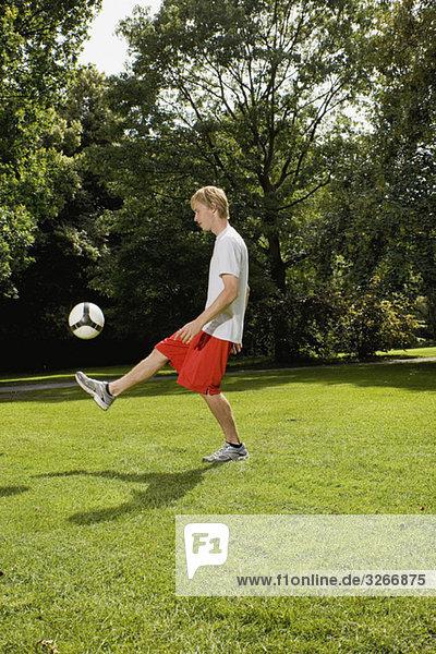 Junger Mann auf dem Rasen  der mit dem Fußball spielt.