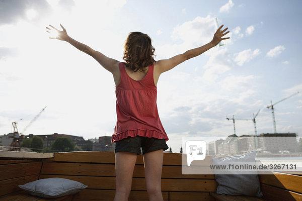 Junge Frau auf dem Motorboot  Arme ausgestreckt  Blick auf das Meer