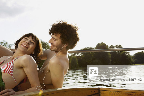 Junges Paar auf dem Motorboot  Mann mit Kopfhörer  Portrait  Nahaufnahme