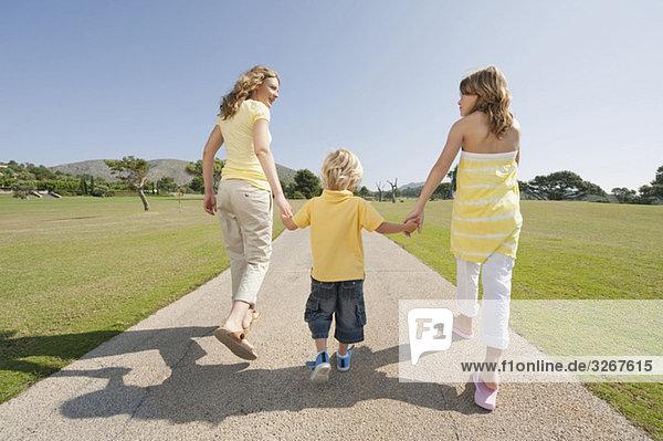 Spanien  Mallorca  Mutter und Kinder (4-5)  (10-11) beim Spaziergang