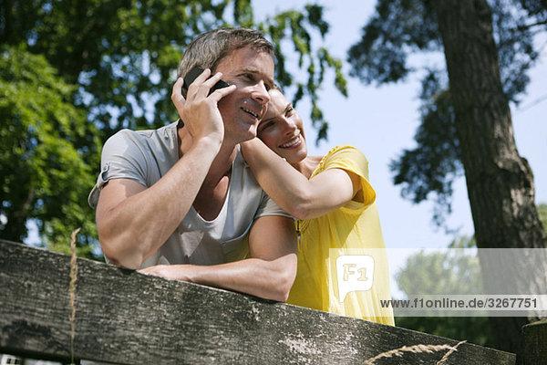 Paar lehnte sich an den Zaun  Mann mit Handy