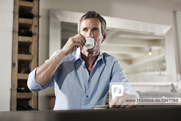 Man sitting at table  drinking cup of espresso