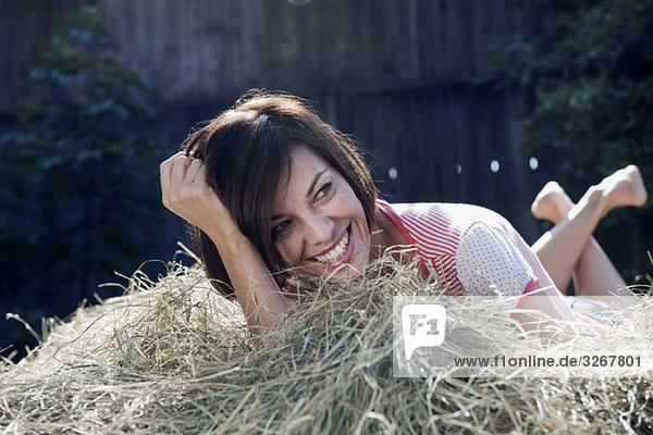 Frau auf dem Heuhaufen liegend  lächelnd  Porträt