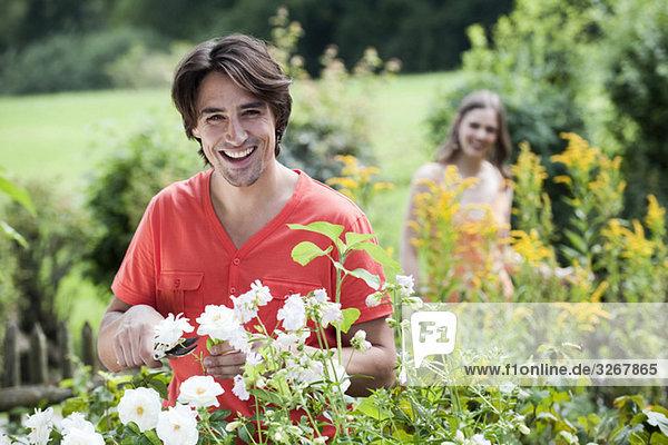 Mann schneidet Blumen  Frau im Hintergrund  lächelnd  Portrait