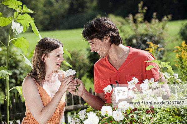 Paar im Garten  Mann schenkt Frau Blume  lächelnd  Portrait