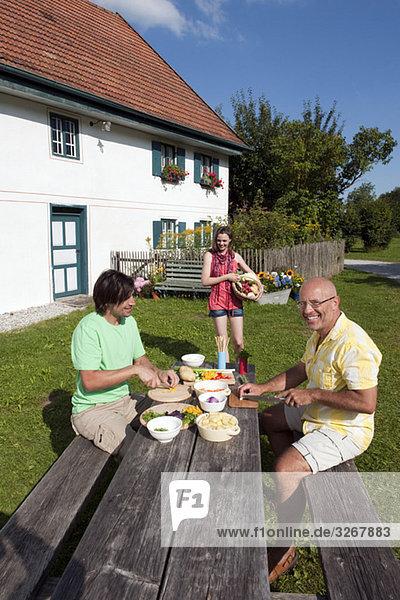 Zwei Männer bei Tisch im Garten  die Essen zubereiten.