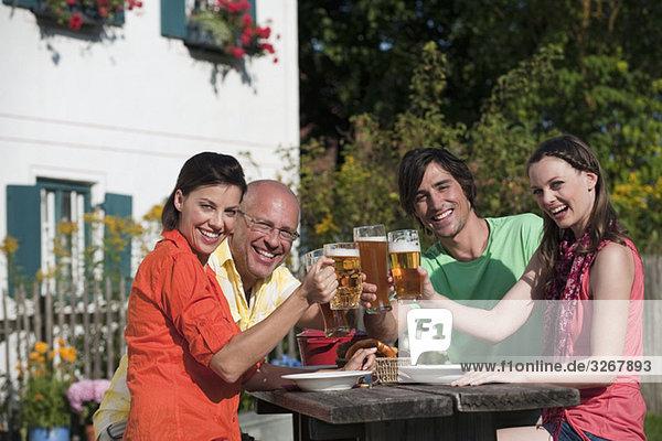 Deutschland  Bayern  Freunde beim Biertrinken im Garten  Gläser klirren