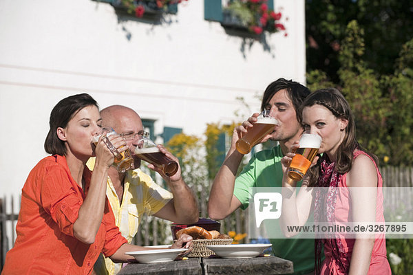 Deutschland  Bayern  Freunde beim Biertrinken im Garten