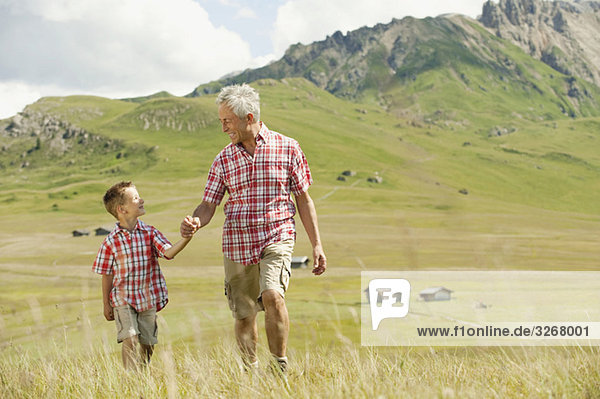 Italy  Seiseralm  Grandfather and grandson (6-7) walking in field