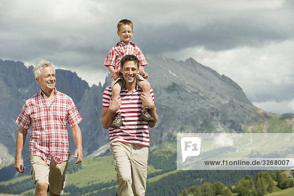Italien  Seiseralm  Großvater  Vater und Sohn (6-7) gehen auf der Wiese  lächelnd  Portrait Italien, Seiseralm, Großvater, Vater und Sohn (6-7) gehen auf der Wiese, lächelnd, Portrait