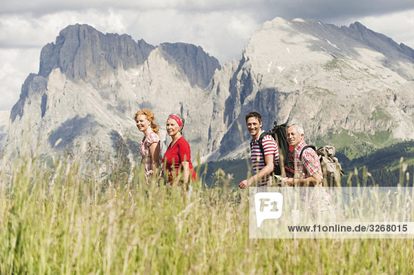 Italien  Seiseralm  Vier Personen wandern  Seitenansicht  lächelnd  Portrait