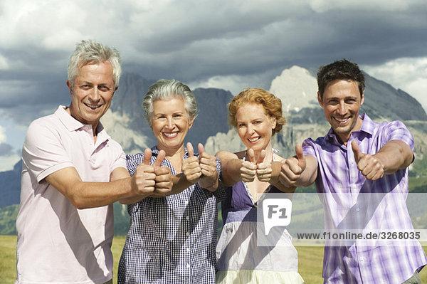 Italien  Seiseralm  Vier Personen  Daumen hoch  lächelnd  Portrait  Nahaufnahme