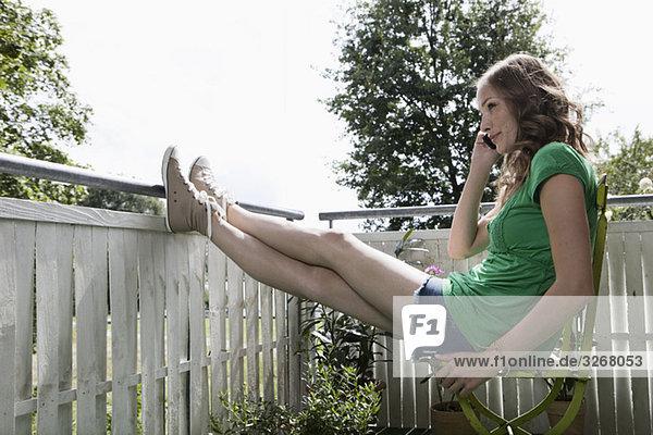 Junge Frau auf dem Balkon sitzend mit dem Handy  lächelnd