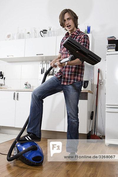 Junger Mann in der Küche mit Staubsauger  Porträt