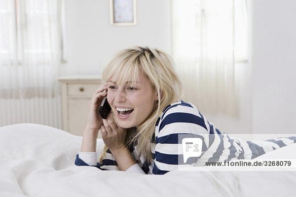 Junge Frau  die mit dem Handy auf dem Bett liegt und lacht.