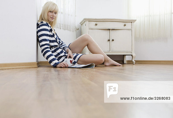 Young woman holding cup sitting on floor  portrait