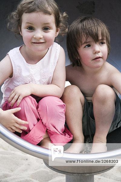Junge und Mädchen (3-4) auf dem Spielplatz  Seite an Seite  Portrait