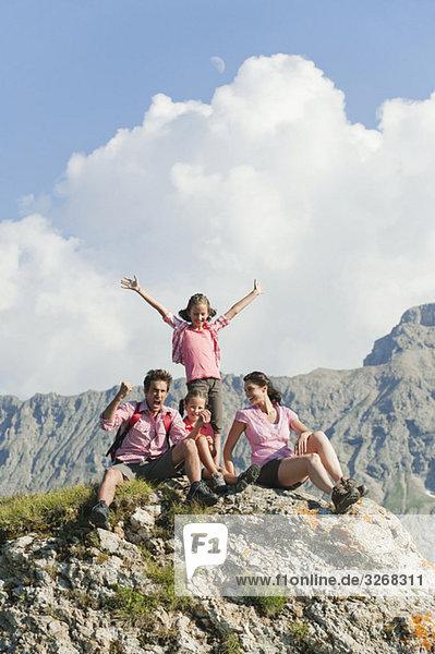 Italien  Südtirol  Familie auf Felsen sitzend  jubelnd  Portrait