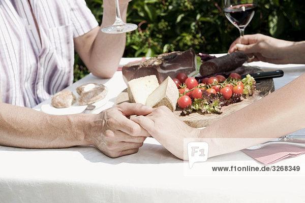 Italien  Südtirol  Paar beim kalten Snack  Händchenhalten  Mittelteil