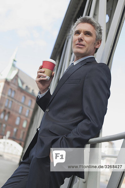Germany  Hamburg  Businessman leaning on railing  holding mug of coffee