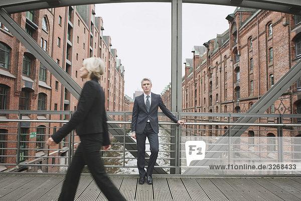 Geschäftsfrau überquert Brücke,  Geschäftsmann im Hintergrund an Geländer gelehnt, Geschäftsfrau überquert Brücke,  Geschäftsmann im Hintergrund an Geländer gelehnt