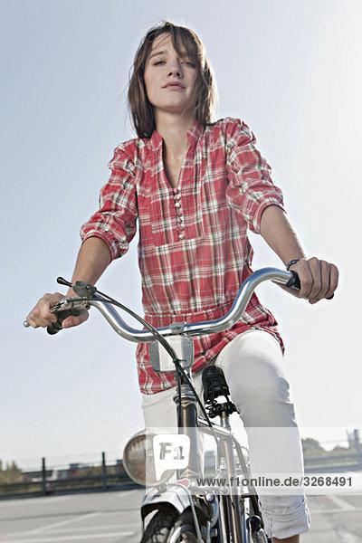 Junge Frau mit Fahrrad auf Parkebene stehend  Portrait Junge Frau mit Fahrrad auf Parkebene stehend, Portrait
