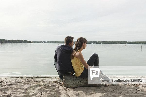 Deutschland  Berlin  Wannsee  Junges Paar am Strand  Rückansicht