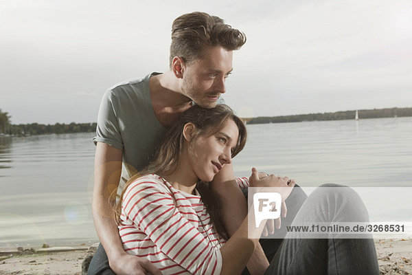 Germany  Berlin  Lake Wannsee  Young couple sitting sitting on lake shore  portrait