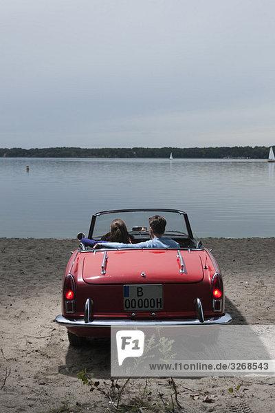 Deutschland  Berlin  Wannsee  Junges Paar im Cabriolet mit Blick auf den See  Rückansicht