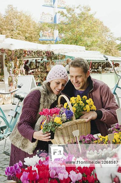 Deutschland  Bayern  München  Paar am Viktualienmarkt bei der Untersuchung von Blumen  Portrait Deutschland, Bayern, München, Paar am Viktualienmarkt bei der Untersuchung von Blumen, Portrait