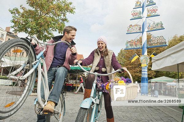 Deutschland  Bayern  München  Viktualienmarkt  Paar mit Fahrrädern  lachend  Portrait