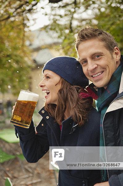 Paar im Biergarten  Frau hält Bierkrug  lachend  Portrait