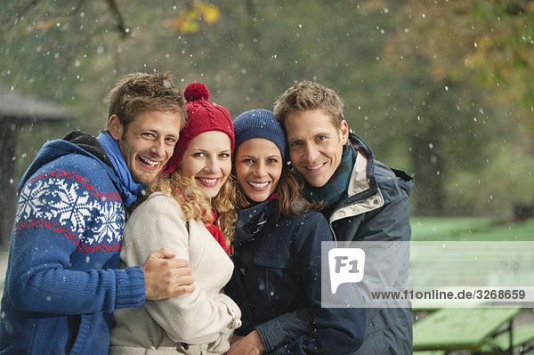 Germany  Bavaria  English Garden  Four persons standing in rainy beer garden  smiling  portrait  close-up
