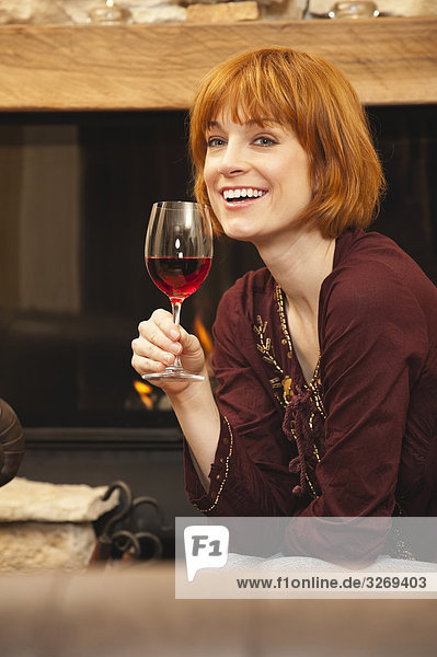 Woman drinking wine by fireplace  smiling  portrait