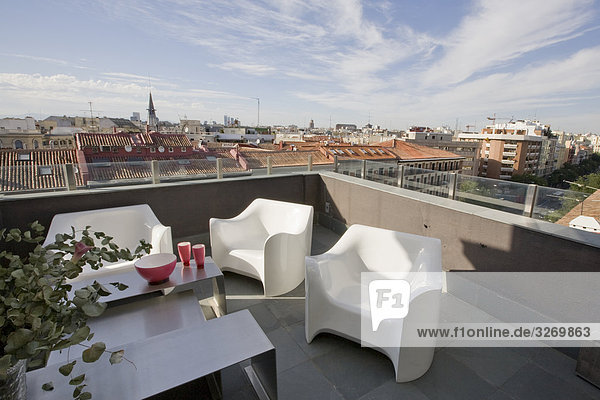 Views of the ceiling of Madrid from a terrace decorated with modern white armchairs  Madrid  Spain