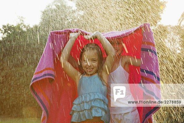Mädchen stehen unter dem Handtuch im Regen