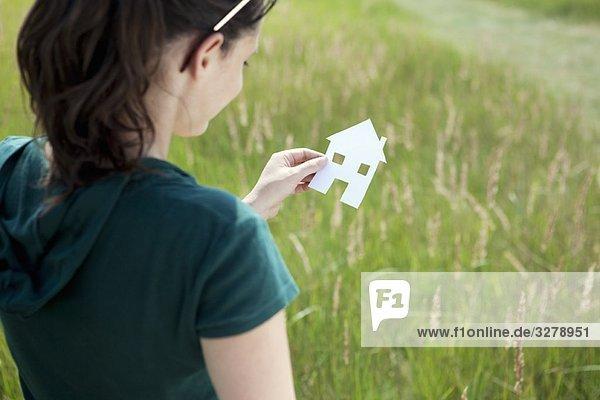 Junge Frau mit ausgeschnittenem Papierhaus