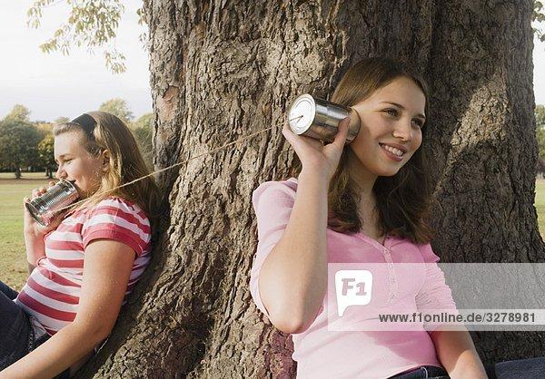 Kinder mit Blechdosentelefonen