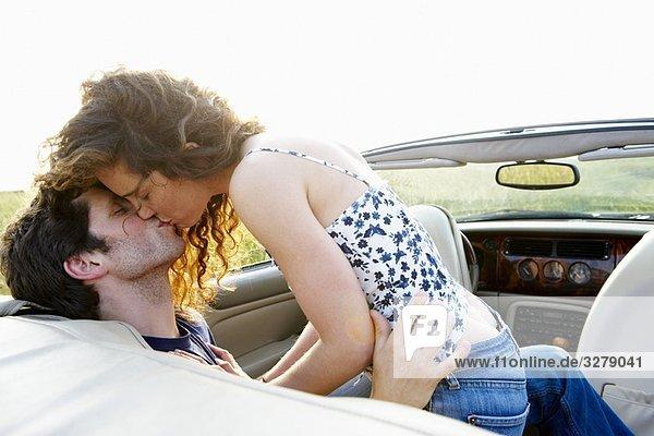 Pärchenküssen in einem Cabriolet